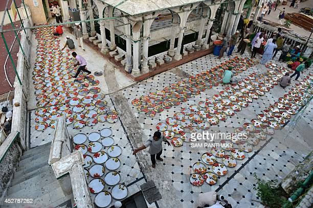 Indian Muslims lay out food for Iftar the breaking of fast during Ramadan at the Alif Ni Masjid in Ahmedabad on July 27 2014 The Iftar for people who...