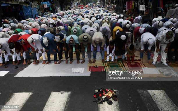 Indian Muslims offer Firday prayers in a street outside a mosque in Kolkata on June 16 2017 Muslims around the world abstain from eating drinking and...