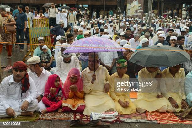 Indian Muslims offer prayers during Eid alFitr outside the Bandra railway station in Mumbai on June 26 2017 Muslims around the world are celebrating...