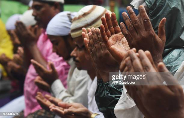 Indian Muslims offer prayers during heavy raining on the last Friday of the holy month of Ramadan outside the Tipu Sultan mosque ahead of the Muslim...