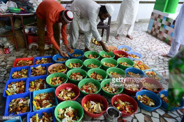 Indian Muslims prepares food to break the fast outside a mosque on the first day of Ramadan in Allahabad on May 28 2017 Like millions of Muslim...