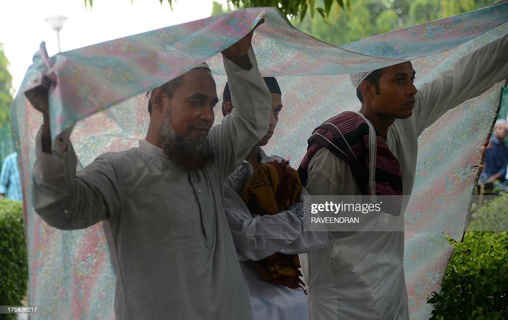 Indian Muslims shelter as they prepare to offer special prayers during a heavy downpour of rain in a public park during celebrations of the Eid al-Fitr festival in New Delhi on August 9, 2013. Muslims around the world are celebrating the Eid al-Fitr , which marks the end of the fasting month of Ramadan.