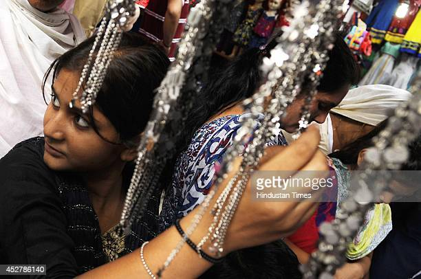 Indian Muslims shop ahead of EidulFitr at a market on July 27 2014 in Noida India Markets across the Muslim world witness huge shopping rush in the...