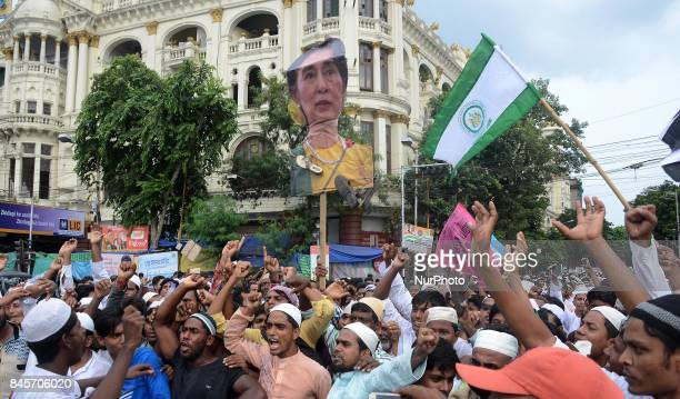 Indian Muslims shout slogans as they hang a sandal across a portrait of Myanmar 's State Counsellor Aung San Suu Kyi during a protest against the...