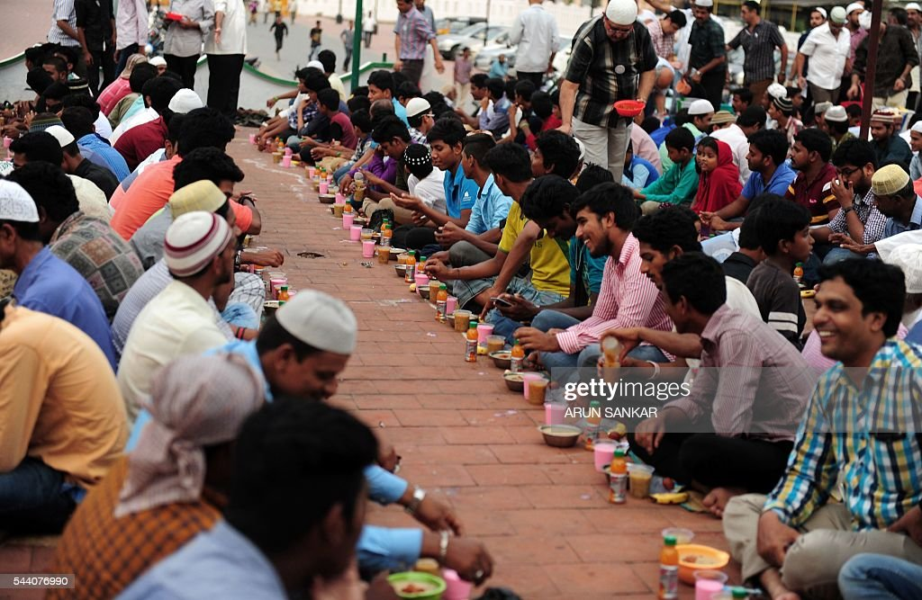 Indian Muslims sit with bowls of porridge(Nombu kanji)as they prepare to break the fast with the Iftar meal during the Islamic month of Ramadan at The Wallajah Big Mosque in Chennai on July 1, 2016.. Across the Muslim world, the faithful fast from dawn to dusk and abstain from eating, drinking, smoking and having sex during that time as they strive to be more pious and charitable. / AFP / ARUN