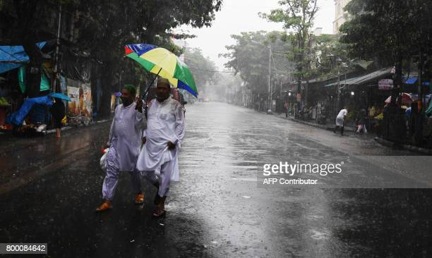 Indian Muslims walk during heavy raining to offer prayers on the last Friday of the holy month of Ramadan outside the Tipu Sultan mosque ahead of the...
