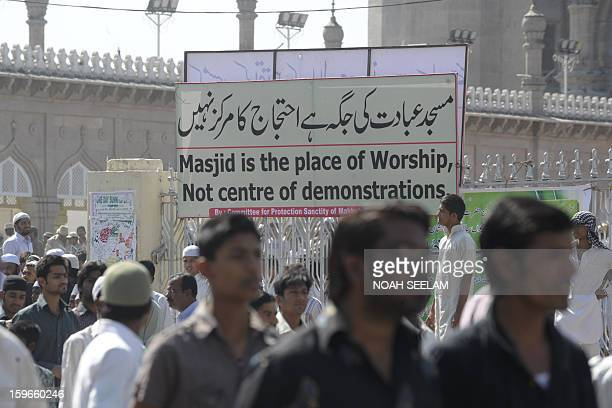 Indian Muslims walk past a banner as they exit the historical Mecca Masjid following congregational Friday prayers in Hyderabad on January 18 2013...