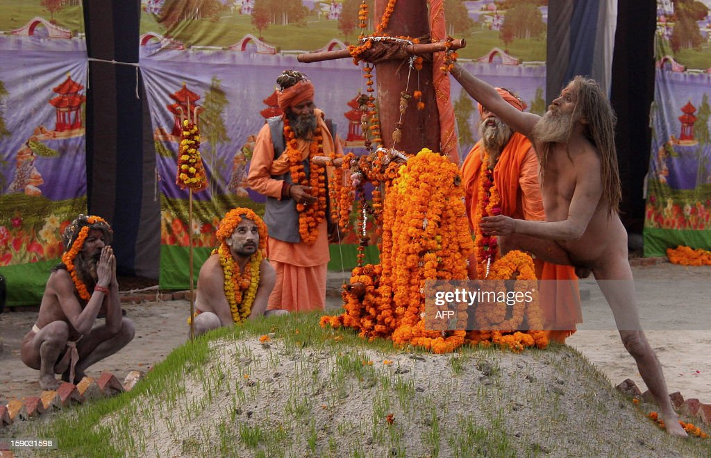 Indian Naga Sadhus - holy men - of Shri Panchayati Anand Akhara perform rituals after a religious procession as the first 'royal entry' for the Kumbh Mela at Sangam in Allahabad on January 6, 2013. The Kumbh Mela, which is scheduled to take place in the northern Indian city in January and February 2013, is the world's largest gathering of people for a religious purpose and millions of people gather for this auspicious occasion. AFP PHOTO/Sanjay KANOJIA