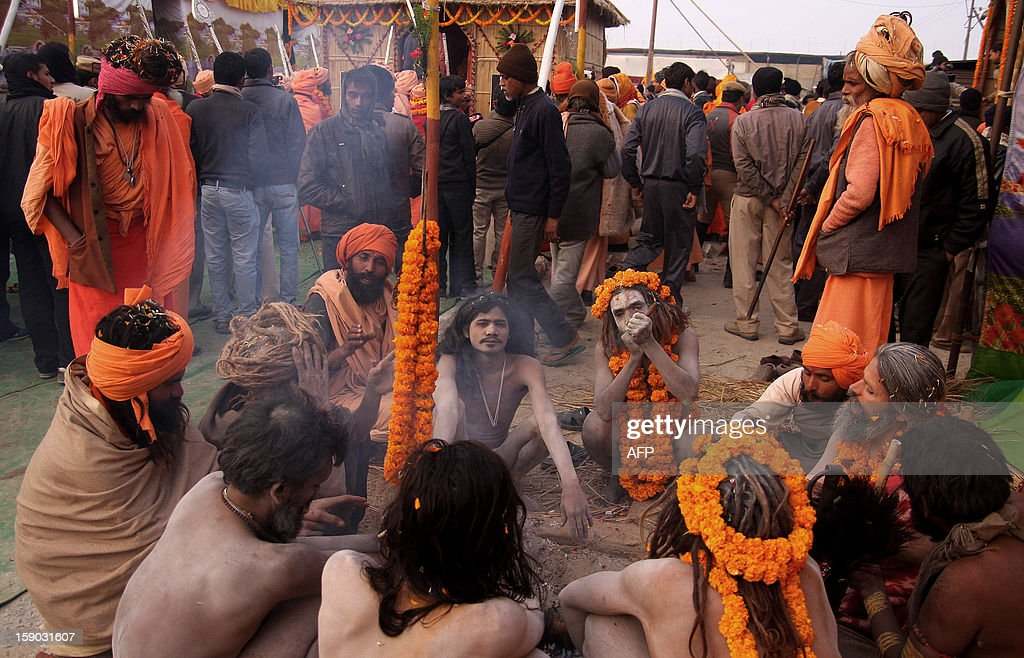 Indian Naga Sadhus - holy men - of Shri Panchayati Anand Akhara warm themselves around a fire after a religious procession as the first 'royal entry' for the Kumbh Mela at Sangam in Allahabad on January 6, 2013. The Kumbh Mela, which is scheduled to take place in the northern Indian city in January and February 2013, is the world's largest gathering of people for a religious purpose and millions of people gather for this auspicious occasion. AFP PHOTO/Sanjay KANOJIA