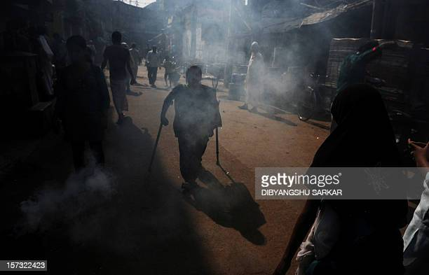 Indian Nahid Parveen a 23 year old polio patient walks through a narrow lane to meet people as a part of her job in an NGO working to empower...