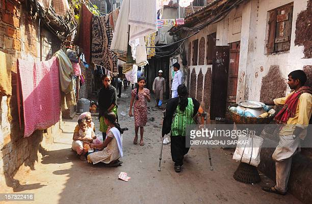 Indian Nahid Parveen a 23 year old polio patient walks through narrow lanes to go to meet people as a part of her job in an NGO working to empower...