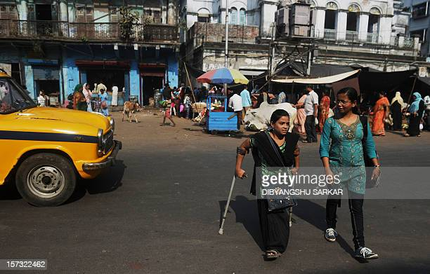 Indian Nahid Parveen a 23 year old polio patient walks with her office colleague as she goes to meet people as a part of her job in a NGO working to...