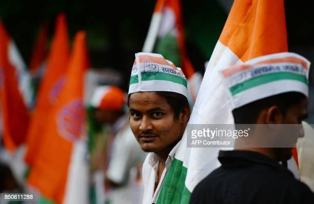 Indian National Congress party activists and supporters hold party flags while forming a human chain during a protest against the increase of fuel...