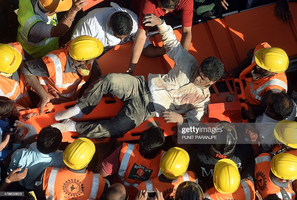 Indian National Disaster Relief Force (NDRF) members and firemen carry a survivor on a stretcher after he was rescued from the debris of a collapsed building in Mumbai on March 14, 2014. An apartment block collapsed in the Indian financial hub Mumbai on March 14, killing one woman and injuring three other people in the latest in a series of deadly building cave-ins, authorities said.