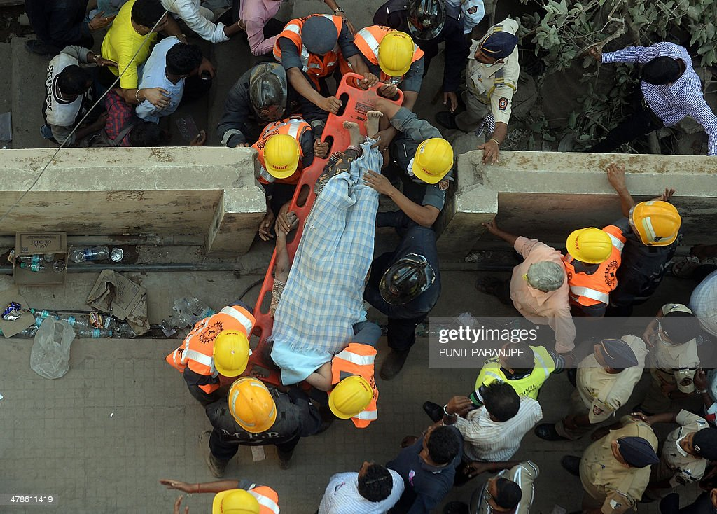 Indian National Disaster Relief Force (NDRF) members and firemen carry a body that was recovered from the debris of a collapsed building in Mumbai on March 14, 2014. An apartment block collapsed in the Indian financial hub Mumbai on March 14, killing one woman and injuring three other people in the latest in a series of deadly building cave-ins, authorities said. AFP PHOTO/ PUNIT PARANJPE