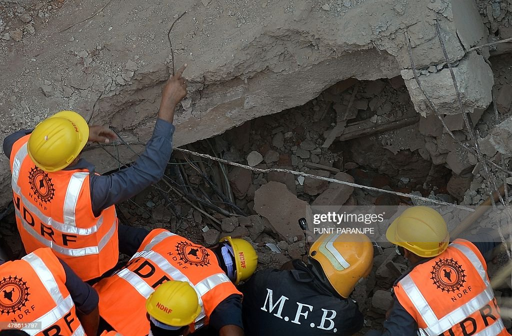 Indian National Disaster Relief Force (NDRF) members and firemen look for survivors in amid the rubble of a collapsed building in Mumbai on March 14, 2014. An apartment block collapsed in the Indian financial hub Mumbai on March 14, killing one woman and injuring three other people in the latest in a series of deadly building cave-ins, authorities said.