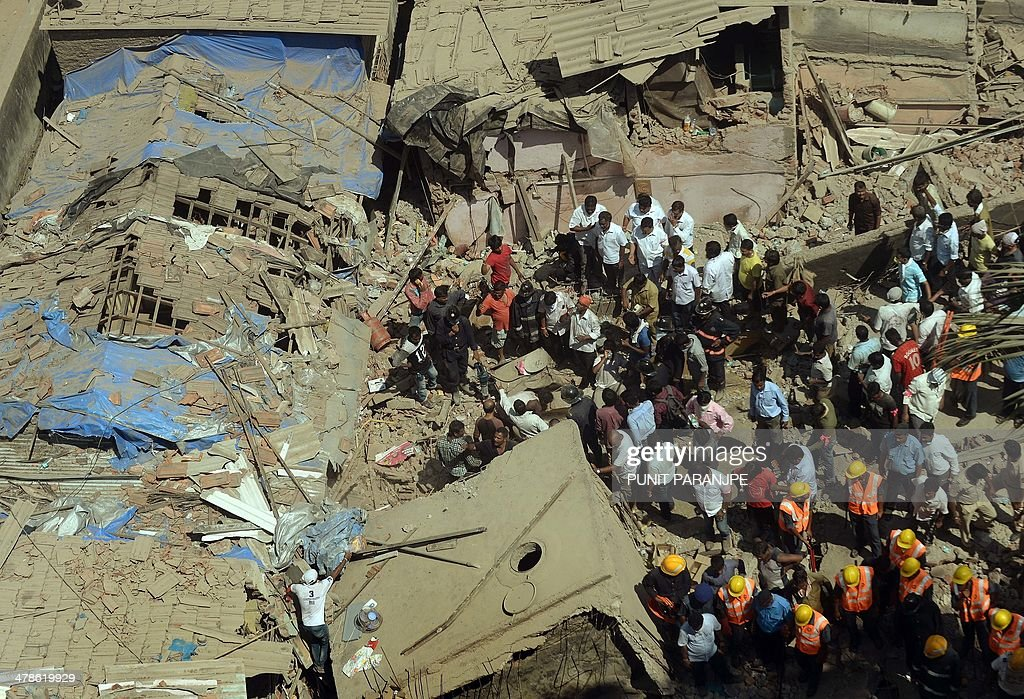 Indian National Disaster Relief Force (NDRF) members and firemen look for survivors from the rubble of a collapsed building in Mumbai on March 14, 2014. An apartment block collapsed in the Indian financial hub Mumbai on March 14, killing one woman and injuring three other people in the latest in a series of deadly building cave-ins, authorities said. AFP PHOTO/ PUNIT PARANJPE