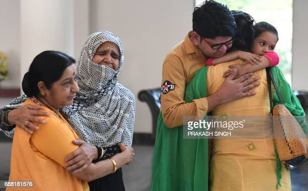 Indian national Uzma Ahmed hugs her brother Wasim and her daughter as Indian Foreign Minister Sushma Swaraj hugs Uzma's mother after her return from...