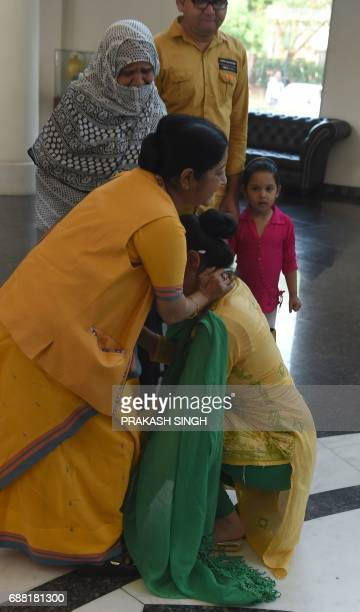 Indian national Uzma Ahmed touches the feet of Indian Foreign Minister Sushma Swaraj after her return from Pakistan at the Foreign Ministry in New...
