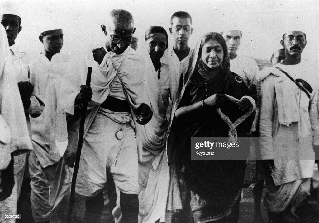 Indian nationalist leader <a gi-track='captionPersonalityLinkClicked' href=/galleries/search?phrase=Mahatma+Gandhi&family=editorial&specificpeople=93728 ng-click='$event.stopPropagation()'>Mahatma Gandhi</a> (Mohandas Karamchand Gandhi), and politician Mrs <a gi-track='captionPersonalityLinkClicked' href=/galleries/search?phrase=Sarojini+Naidu+-+Poeta&family=editorial&specificpeople=931956 ng-click='$event.stopPropagation()'>Sarojini Naidu</a>, with a garland, during the Salt March protesting against the government monopoly on salt production.