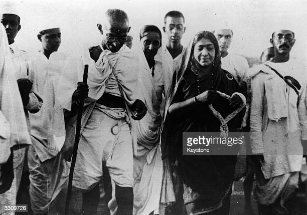 Indian nationalist leader Mahatma Gandhi and politician Mrs Sarojini Naidu with a garland during the Salt March protesting against the government...