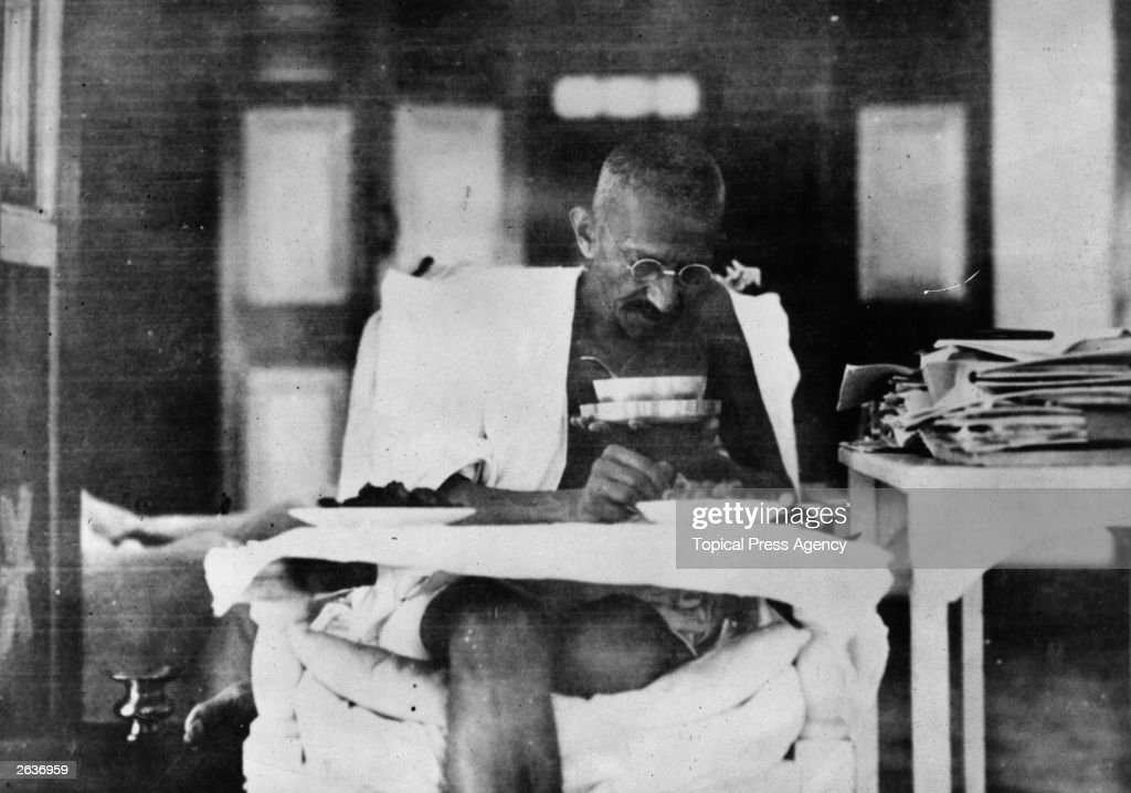 Indian nationalist leader Mahatma Gandhi eating at his home whilst living in seclusion after his release from prison by the British authorities