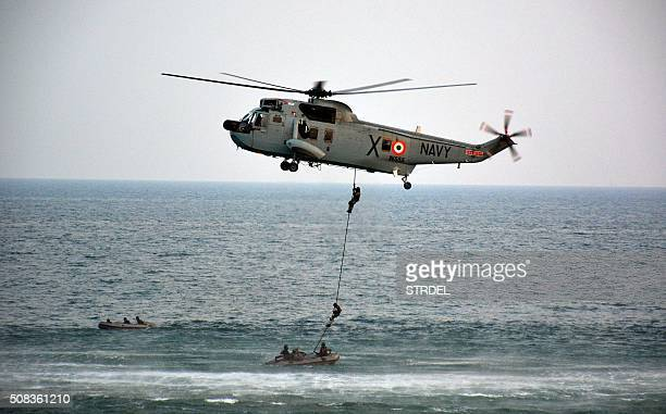 Indian Navy personnel abseil from a helicopter as they take part in a demonstration routine ahead of the International Fleet Review in Visakhapatnam...