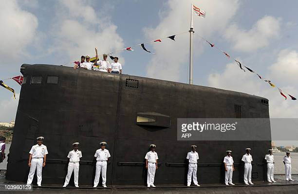 Indian navy personnel and officials hold the Commonwealth Games baton on board INS Sindhuvijay submarine as it arrives at the naval base in Mumbai on...