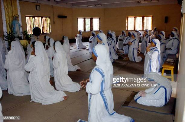 Indian nuns of the Missionaries of Charity take part in a special prayer for the recovery of Pope John Paul II sitting beside a statue of Mother...