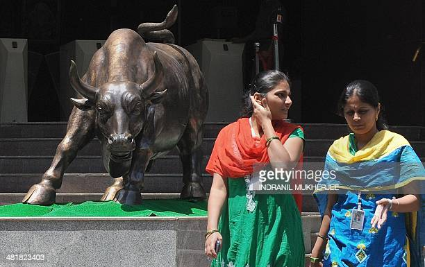 Indian office goers walk past the bronze bull outside the Bombay Stock Exchange during intraday trade in Mumbai on April 1 2014 India's central bank...