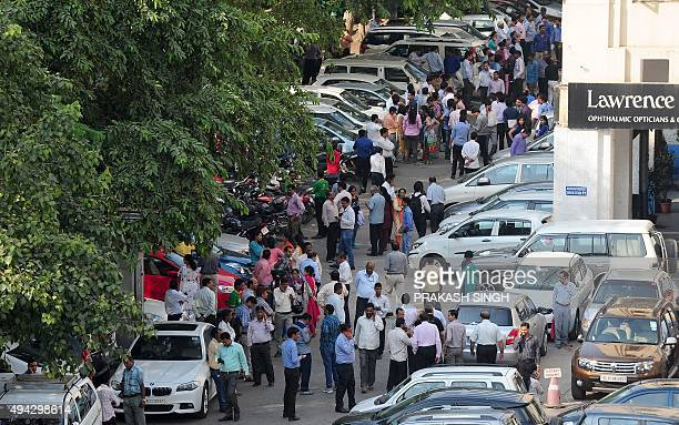 Indian office workers stand in an open area in a carpark following an earthquake in New Delhi on October 26 2015 A strong earthquake lasting almost a...