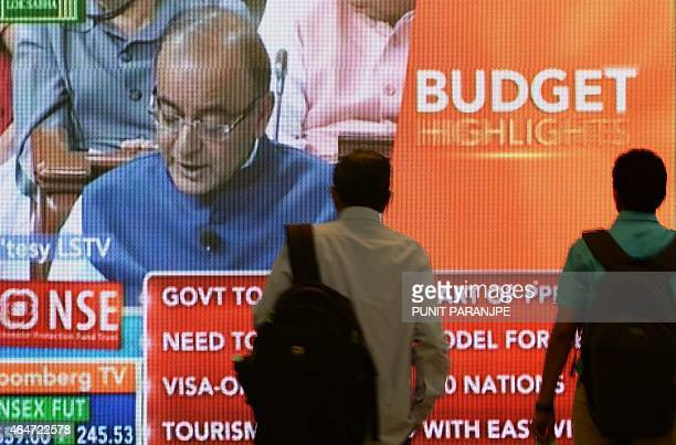 Indian officegoers walk past a digital screen showing Indian Finance Minister Arun Jaitley delivering his Budget speech at Parliament in New Delhi on...