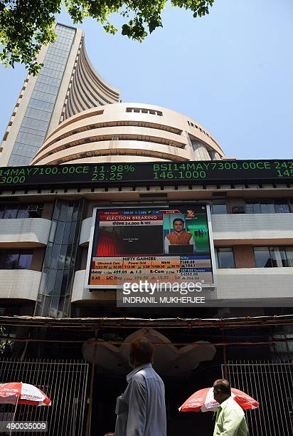 Indian officegoers walk past the Bombay Stock Exchange as the digital broadcast shows the 30 share benchmark index SENSEX cross 24000 points during...