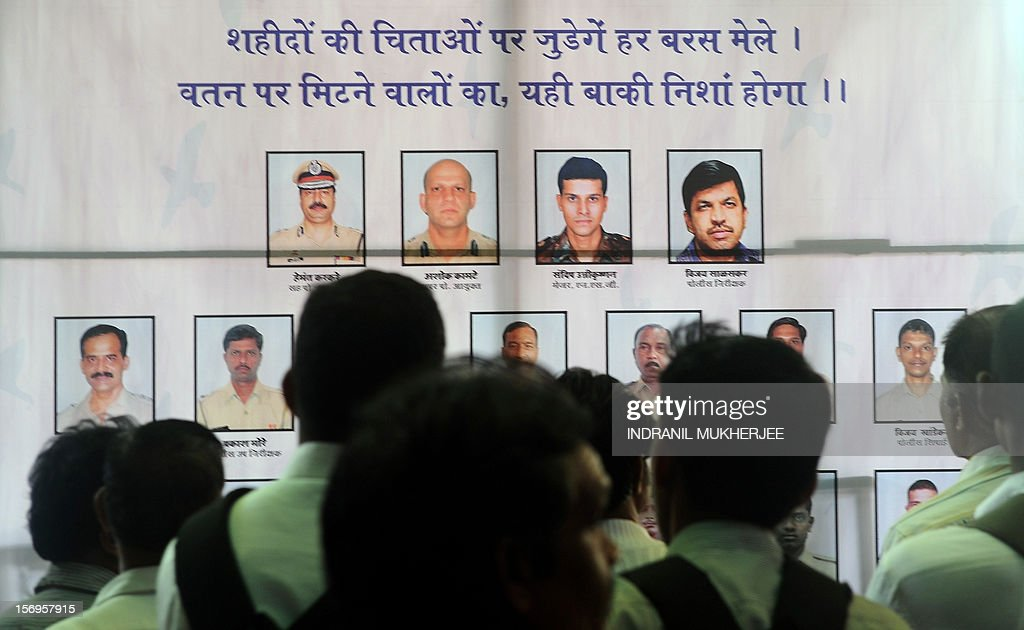 Indian officer workers pay their respects to police and uniformed personnel who lost their lives in 2008 terror attacks outside a railway station in Mumbai on November 26, 2012. A total of 166 people were killed and more than 300 others were injured when 10 heavily-armed Islamist militants stormed the city on November 26, 2008, attacking a number of sites, including the city's main railway station, two luxury hotels, a popular tourist restaurant and a Jewish centre.