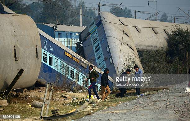 TOPSHOT Indian officials and bystanders gather at the derailed train carriages at Rura some 30 kms west of Kanpur on December 28 following a train...
