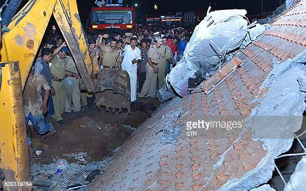 Indian officials and bystanders gather beside a collapsed building after an explosion and fire at The Puttingal Devi Temple in Paravur early April 10...