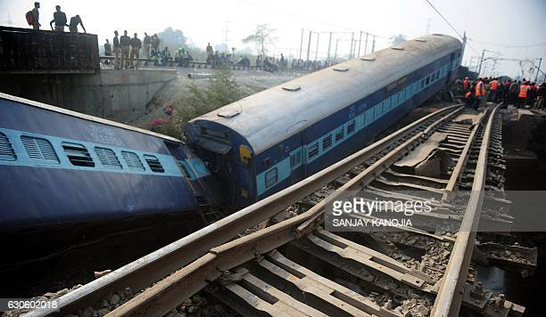 TOPSHOT Indian officials and bystanders gather beside the wreckage of train carriages at Rura some 30kms west of Kanpur on December 28 following a...