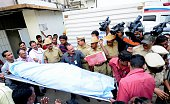 Indian officials carry the body of 38yearold Bhavani Devi from a hospital in Bangalore on December 29 after she succumbed to her injuries following a...