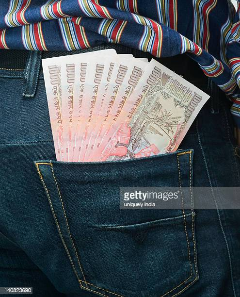 Indian one thousand rupee notes protruding from a jeans pocket