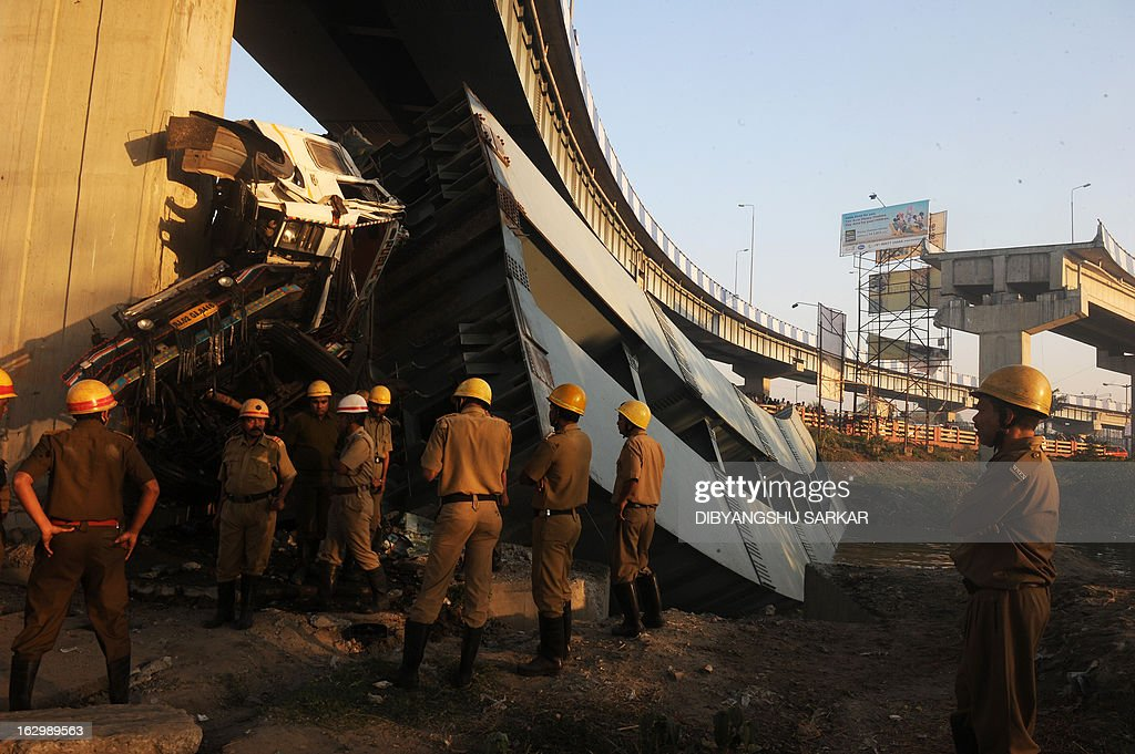 Indian onlookers and firefighters stand near the collapsed portion of the flyover in Kolkata on March 3, 2013. A huge portion of a flyover on the eastern side of the Indian metropolis collapsed leaving three persons injured, the flyover connects the airport with Eastern Metropolitan Bypass and the eastern and southern suburbs. As the debris fell into a canal running below the flyover, it took down a truck the driver and two others were rescued from the canal by fire-brigade personnel and locals. AFP PHOTO/Dibyangshu SARKAR