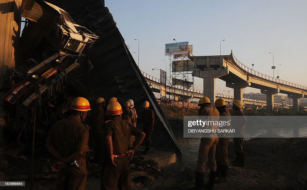 Indian onlookers and firefighters stand near the collapsed portion of a flyover in Kolkata on March 3, 2013. A huge portion of a flyover on the eastern side of the Indian metropolis collapsed leaving three persons injured, the flyover connects the airport with Eastern Metropolitan Bypass and the eastern and southern suburbs. As the debris fell into a canal running below the flyover, it took down a truck the driver and two others were rescued from the canal by fire-brigade personnel and locals. AFP PHOTO/Dibyangshu SARKAR