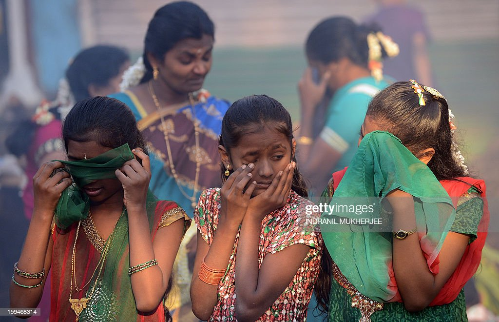 Indian onlookers react from the smoke as a traditional sweet dish is cooked on open fires during the Pongal festival in Mumbai on January 14, 2013. Pongal is a thanksgiving or harvest festival celebrated by people hailing from the Indian state of Tamil Nadu. Pongal-which coincides with the Hindu festival Makara Sankranthi and is celebrated throughout India as the winter harvest, is usually held from January 13–16. AFP PHOTO/ INDRANIL MUKHERJEE
