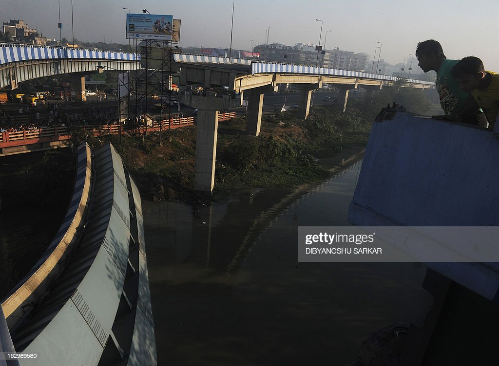 Indian onlookers stand near the collapsed portion of a flyover in Kolkata on March 3, 2013. A huge portion of a flyover on the eastern side of the Indian metropolis collapsed leaving three persons injured, the flyover connects the airport with Eastern Metropolitan Bypass and the eastern and southern suburbs. As the debris fell into a canal running below the flyover, it took down a truck the driver and two others were rescued from the canal by fire-brigade personnel and locals. AFP PHOTO/Dibyangshu SARKAR