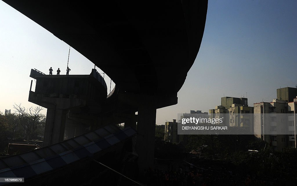Indian onlookers stand near the collapsed portion of the flyover in Kolkata on March 3, 2013. A huge portion of a flyover on the eastern side of the Indian metropolis collapsed leaving three persons injured, the flyover connects the airport with Eastern Metropolitan Bypass and the eastern and southern suburbs. As the debris fell into a canal running below the flyover, it took down a truck the driver and two others were rescued from the canal by fire-brigade personnel and locals. AFP PHOTO/Dibyangshu SARKAR