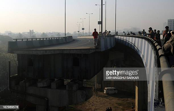 Indian onlookers stand near the collapsed portion of the flyover in Kolkata on March 3 2013 A huge portion of a flyover on the eastern side of the...