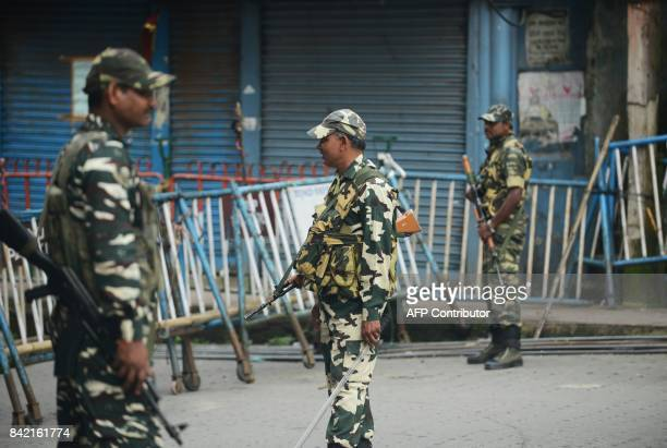 Indian paramilitary forces stand guard along a road during the 83th day of an indefinite strike called by the Gorkha Janmukti Morcha for separate...