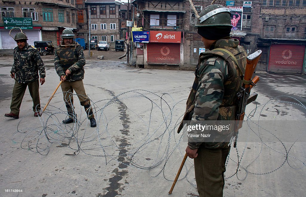 Indian paramilitary forces stand guard in front the concertina razor wire during a strict curfew on the seventh consecutive day, imposed after the execution of alleged Indian parliament attacker Mohammad Afzal Guru on February 15, 2013 in Srinagar, the summer capital of Indian Administered Kashmir, India. Afzal Guru, from Sopore town in the north of Kashmir, was hung on February 09 for his role in the 2001 Indian parliament attack which left 14 dead. The hanging has further strained relations between India - who blamed the attack on 'Pakistan backed' militant group Jaish-e-Mohammed - and neighbouring Pakistan and has seen an military increase from both along the border.Curfew was lifted from some parts of Srinagar after four days.