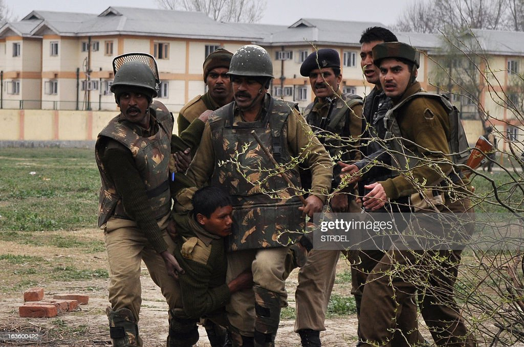 Indian paramilitary personnel carry an injured comrade on a stretcher at a school compound in Srinagar on March 13, 2013. Five paramilitary police were killed March 13 in an ambush on security forces in the main city of Indian Kashmir carried out by two militants who were then shot dead, a senior officer said.