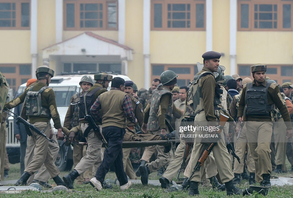 Indian paramilitary personnel carry away a fallen comrade on a stretcher at a school compound in Srinagar on March 13, 2013. Five paramilitary police were killed March 13 in an ambush on security forces in the main city of Indian Kashmir carried out by two militants who were then shot dead, a senior officer said. AFP PHOTO/Tauseef MUSTAFA