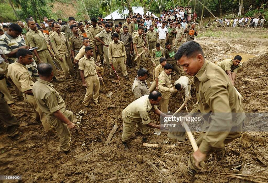 Indian paramilitary personnel dig through mud during a rescue operation after a landslide at Ujan Mudipara village in Baramura hills, 70 kms north of Agartala on May 9, 2013. Two bodies were recovered from the landslide. Cyclonic storms accompanied by lightning and rain continued to create havoc in Tripura for the fifth day, killing seven people, including five women and injuring 20 others, officials said